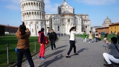Leaning Tower in Piazza dei Miracoli also known as Piazza del Duomo with tourists, Pisa, Italy