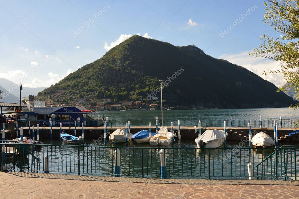 SULZANO, ITALY - MAY 13, 2017: harbor of Sulzano town with boats on Lake Iseo with Monte Isola on the background, Italy