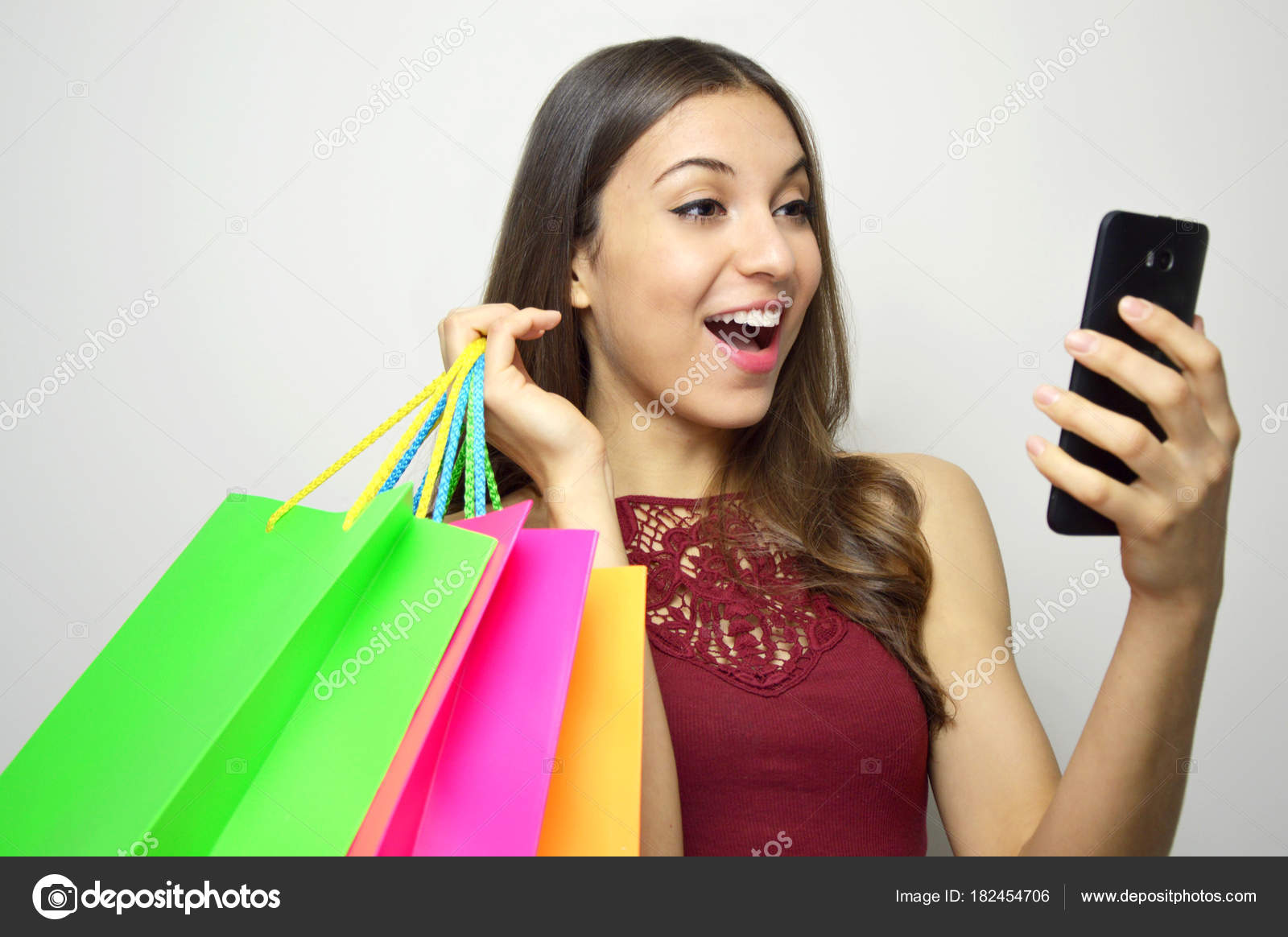 9ec42fd918e9d Attractive woman with smart phone and shopper bags in her hands looking to  the side at your brand or product on white background. Copy space.