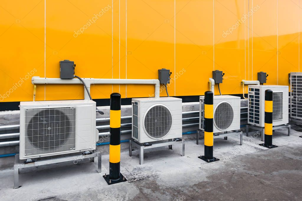 air conditioner compressor installed outside building with yello