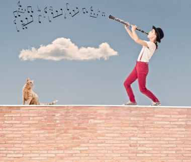 little girl playing clarinet on the top of a bricks wall