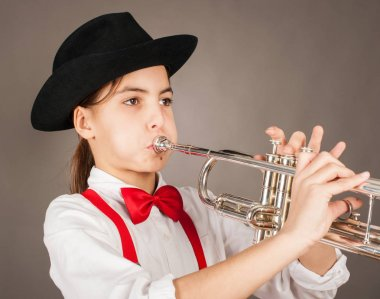 little girl playing trumpet on a gray background