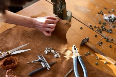 Female artisan working on manual vintage machine for leather surrounded with tools