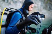 Potápěč ve vodě s fotoaparátem