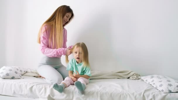 Happy young mother and daughter playing, drawing, playing games on your smartphone braid braids, read.