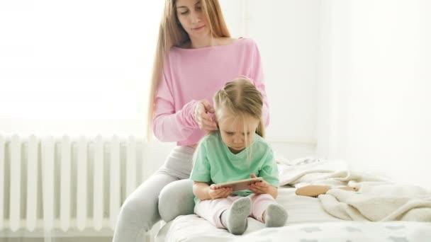 Šťastná mladá matka a dcera, hraní, kreslení, hraní her na smartphonu COP copánky, přečtěte si.