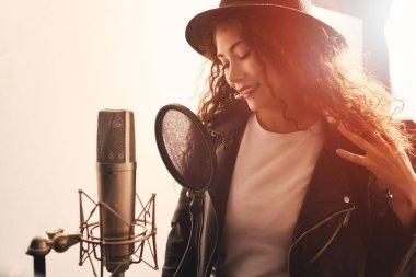 Pretty female singer recording in music studio