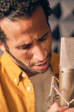 Man passionately singing in recording studio