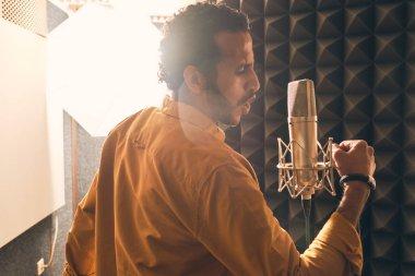 Moroccan man recording vocals in studio