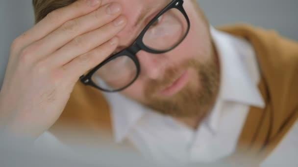 A férfi fáradt a munkában, stresszesnek tűnik.