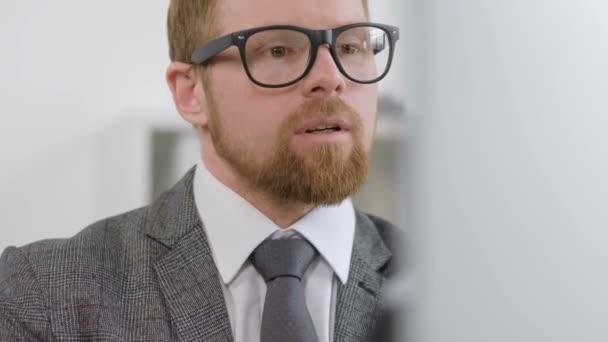 Szemüveges férfi számítógépes munkában.