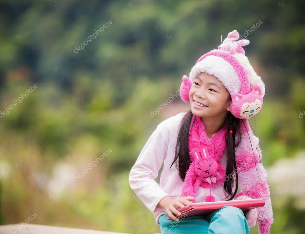 Funny little Asian girl learning with tablet pc