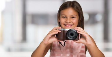 little girl holding a compact camera