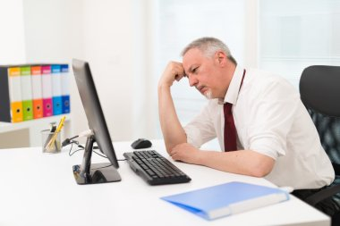 Stressed businessman looking at computer