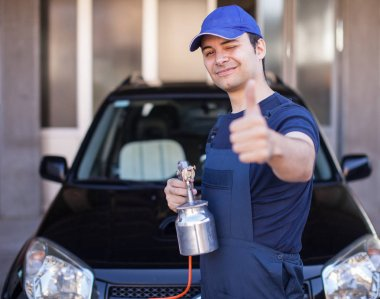 Car body repairer holding spray gun
