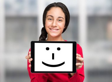 girl holding a smiling tablet