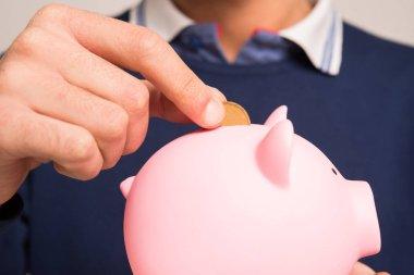 Man putting money in piggy bank