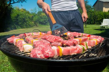 Man preparing meat on grill