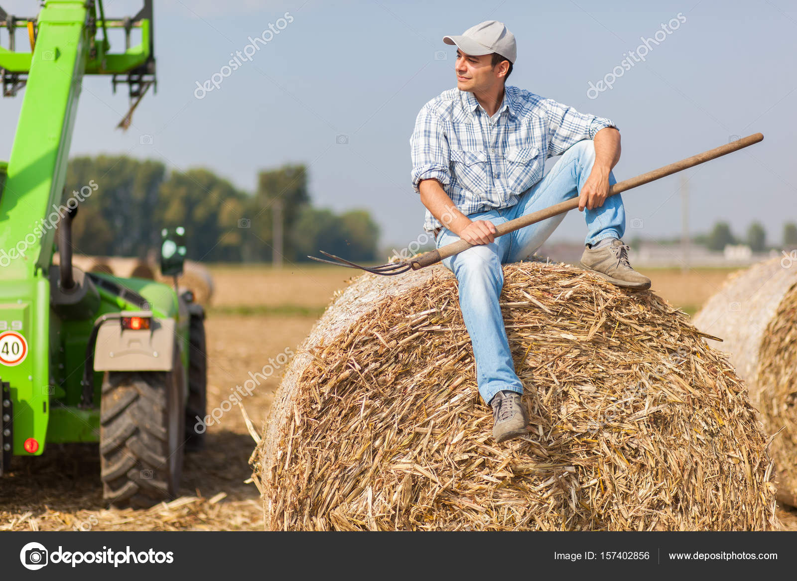 Coltivatore sorridente che si siede su una balla di fieno for Piani di casa di balla di fieno