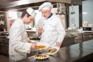 Chefs preparing dish in a kitchen