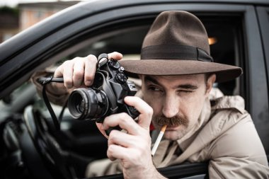 Spy or paparazzo photographer, detective using camera in his car