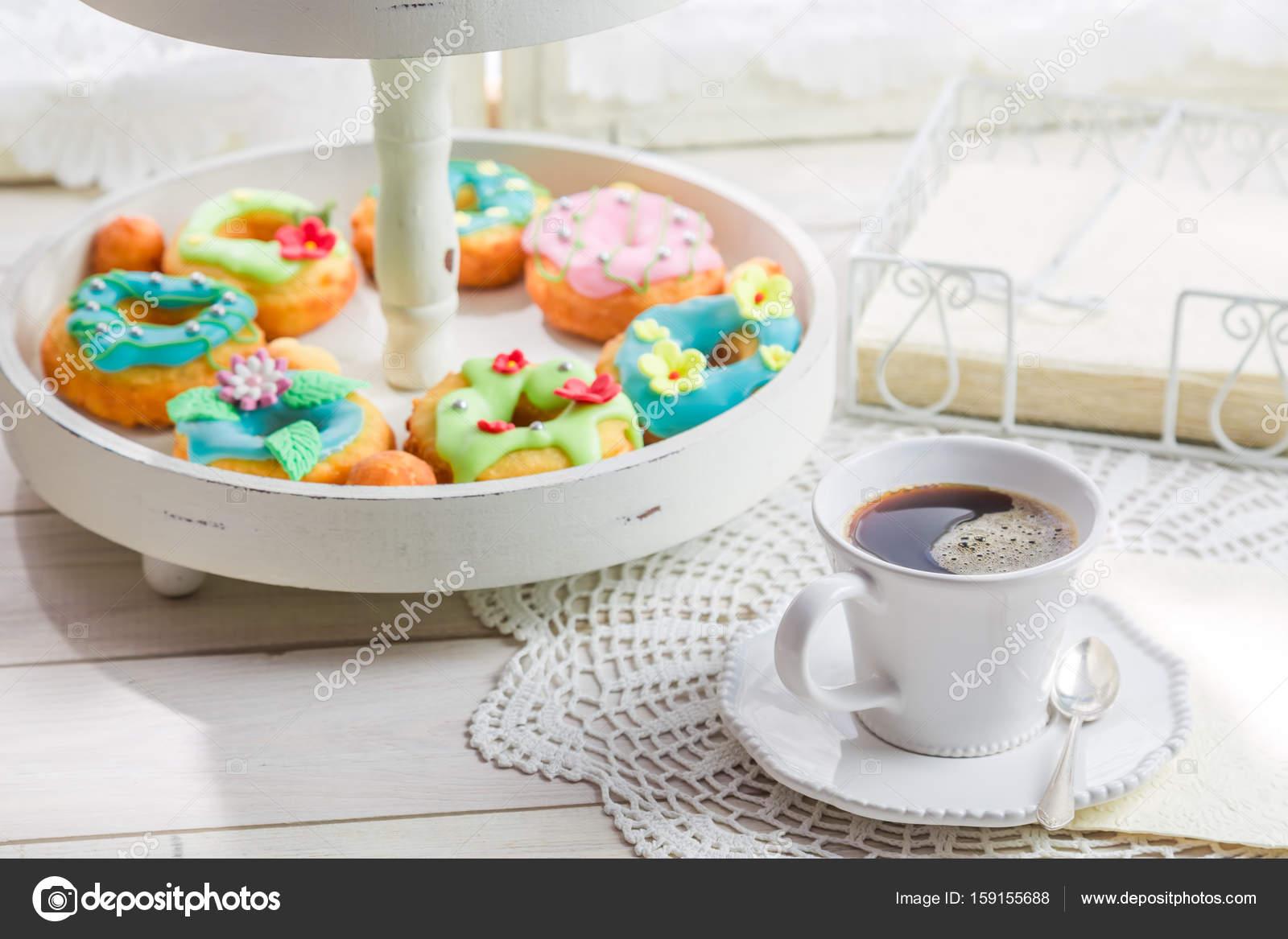 Kaffee und Donuts mit bunter Dekoration auf weißen Tisch — Stockfoto ...