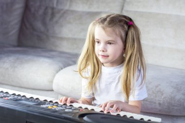 Child playing piano. Side view of a child playing piano