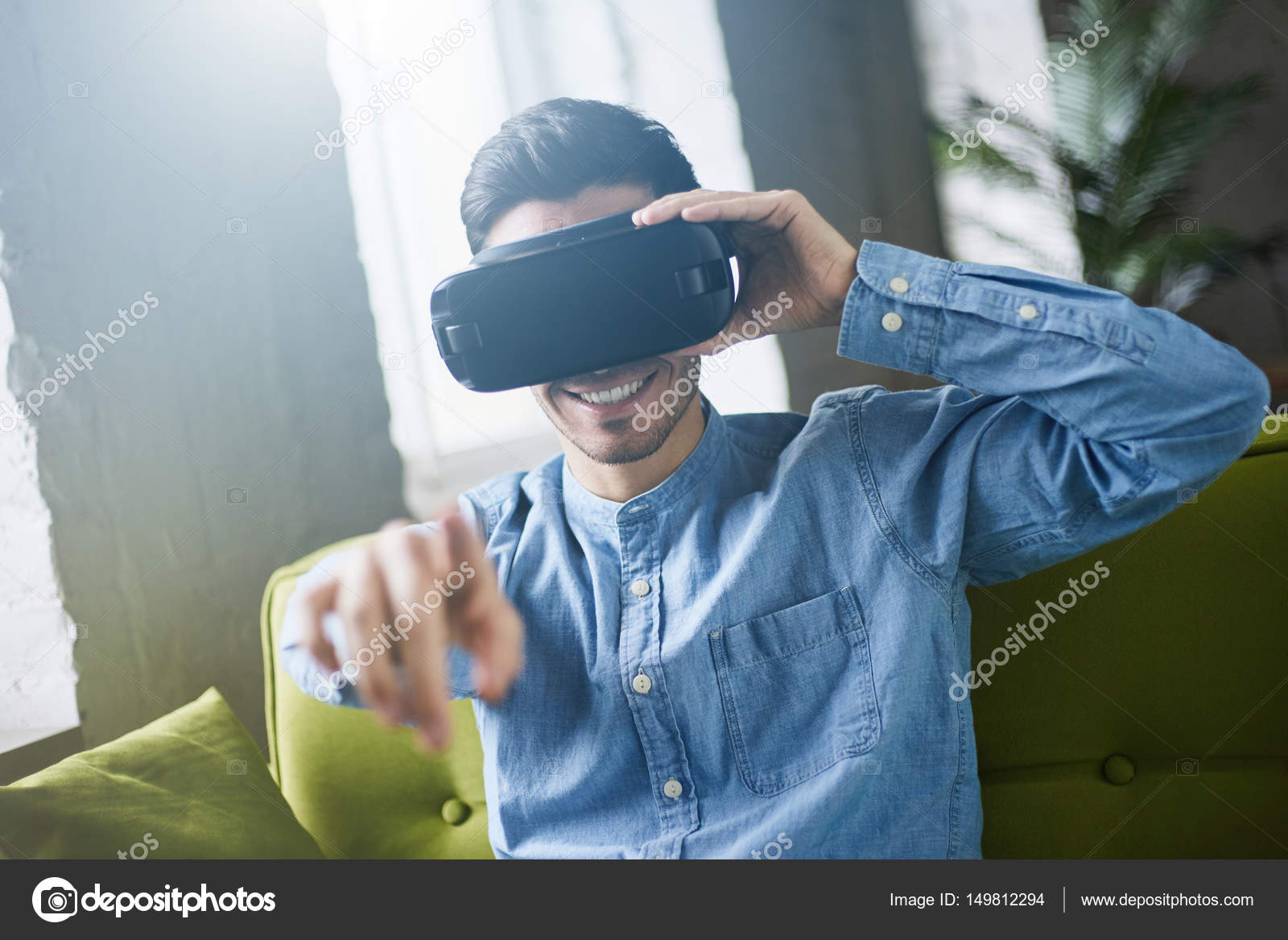 9b9ee9a54a2 VR glasses. Smiling young caucasian in blue denim shirt man in virtual  reality headset or 3d glasses pointing with finger in the air