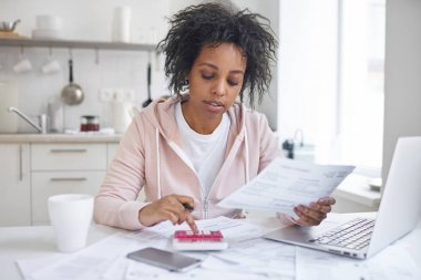 Financial literacy concept. Indoor shot of young single african american female student sitting at kitchen table, calculating expences, trying to analyze domestic dudget, thinking how to pay debt