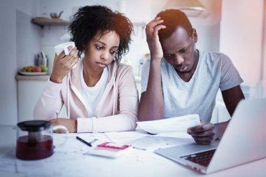 Stressed african american couple reviewing their finances sitting at kitchen table: wife and husband making calculations with papers and laptop. People and finances concept. Family budget and debts