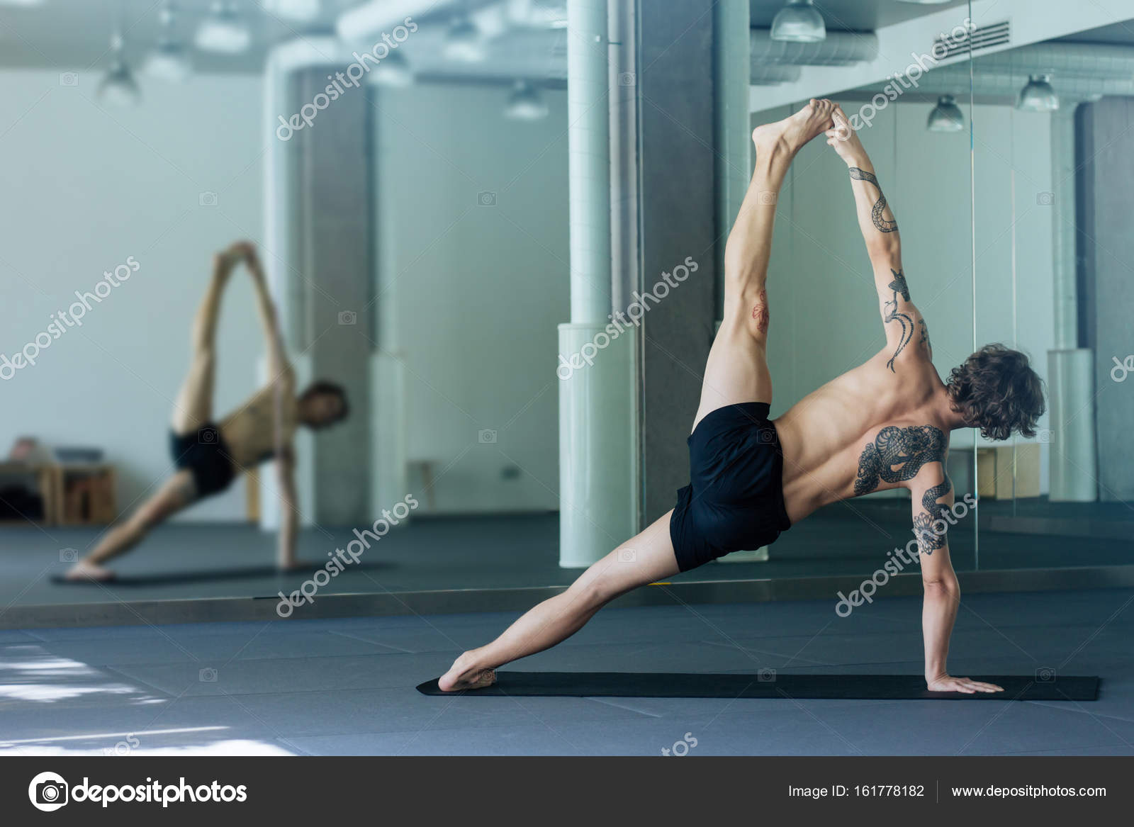 Handsome Tattooed Man Practicing Yoga Young Male Teacher Takin Stock Photo C Hozard 161778182