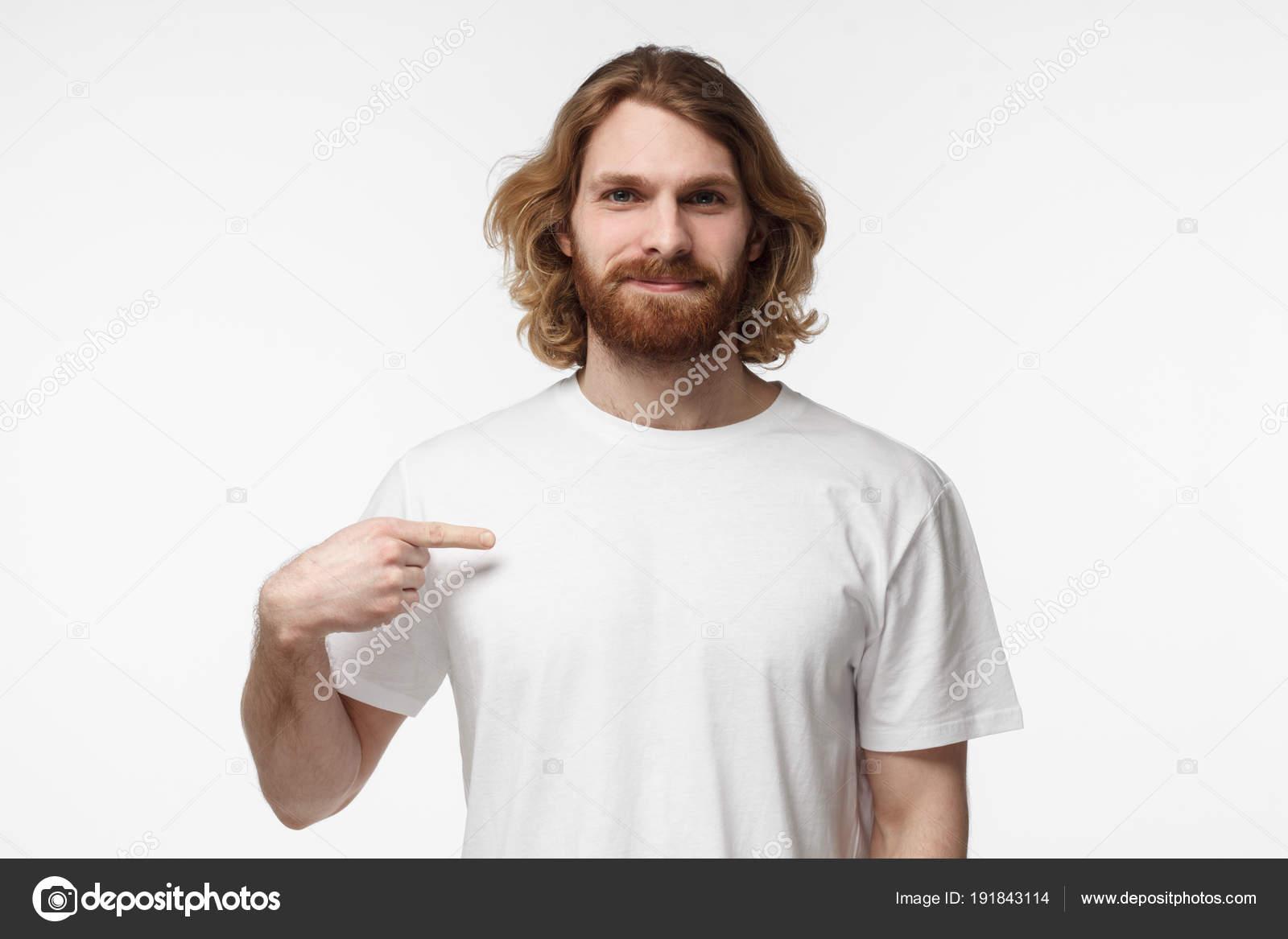 3f30a3ff257ee Joven barbudo a hombre apuntando con el dedo índice en la camiseta blanca  en blanco con espacio vacío ...