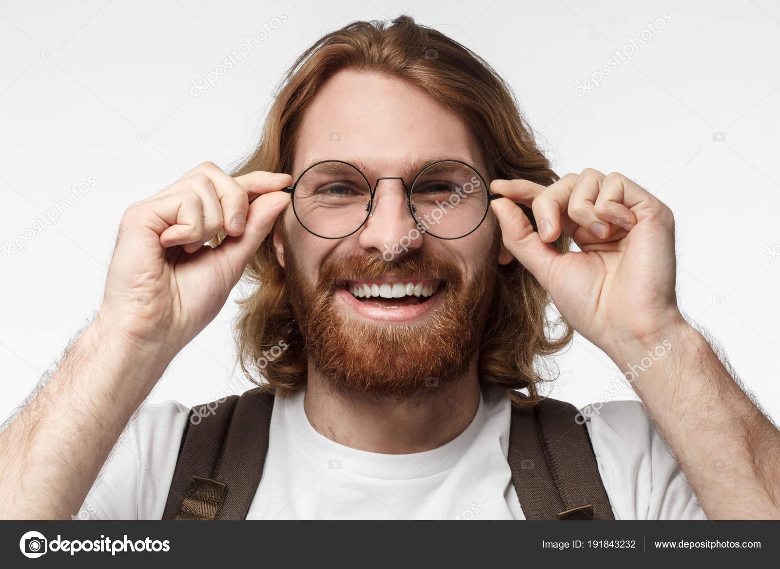 Close-up do jovem atraente isolado em um fundo cinza, usando grandes óculos  redondos ba15354bfe