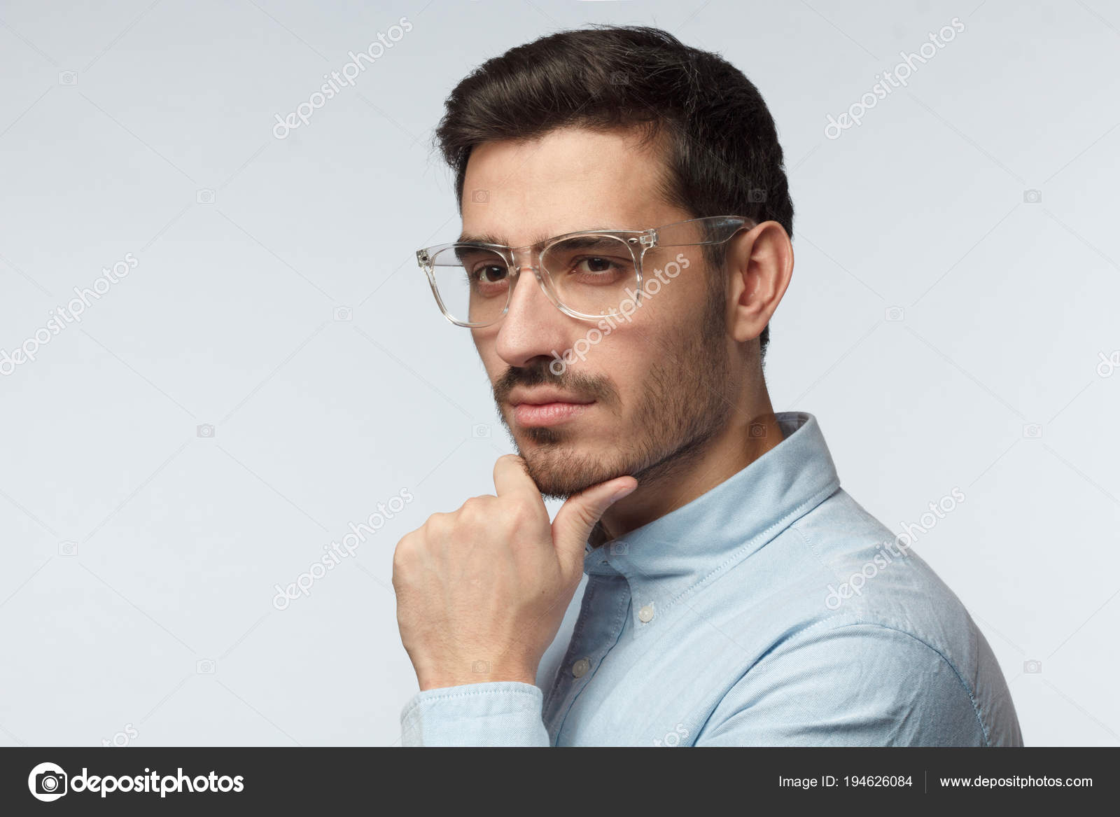 4775a43d2899 Studio closeup of young European Caucasian man pictured isolated on grey  background wearing short haircut and plastic transparent eyeglasses