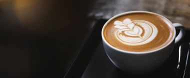 Close up of hot latte coffee in the cafe, photo banner for website header design with copy space for text
