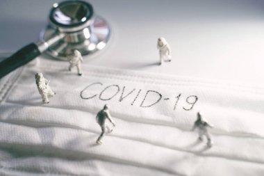 Koruyucu kıyafetli minyatür doktorlar Covid-19 ve Coronavirus salgınlarını önlüyor. Üzerinde stetoskopla yazılmış Covid-19 yazılı cerrahi maske.