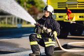 Fotografie hasič rozlití vody v zóna spalování