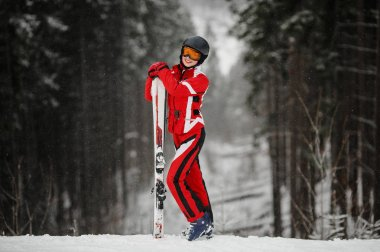 Girl in mask stands and holds ski