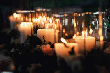 many candles in glass vases