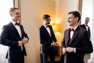 stylish groom laughing and having fun with groomsmen while getting ready in the morning for wedding ceremony. luxury man