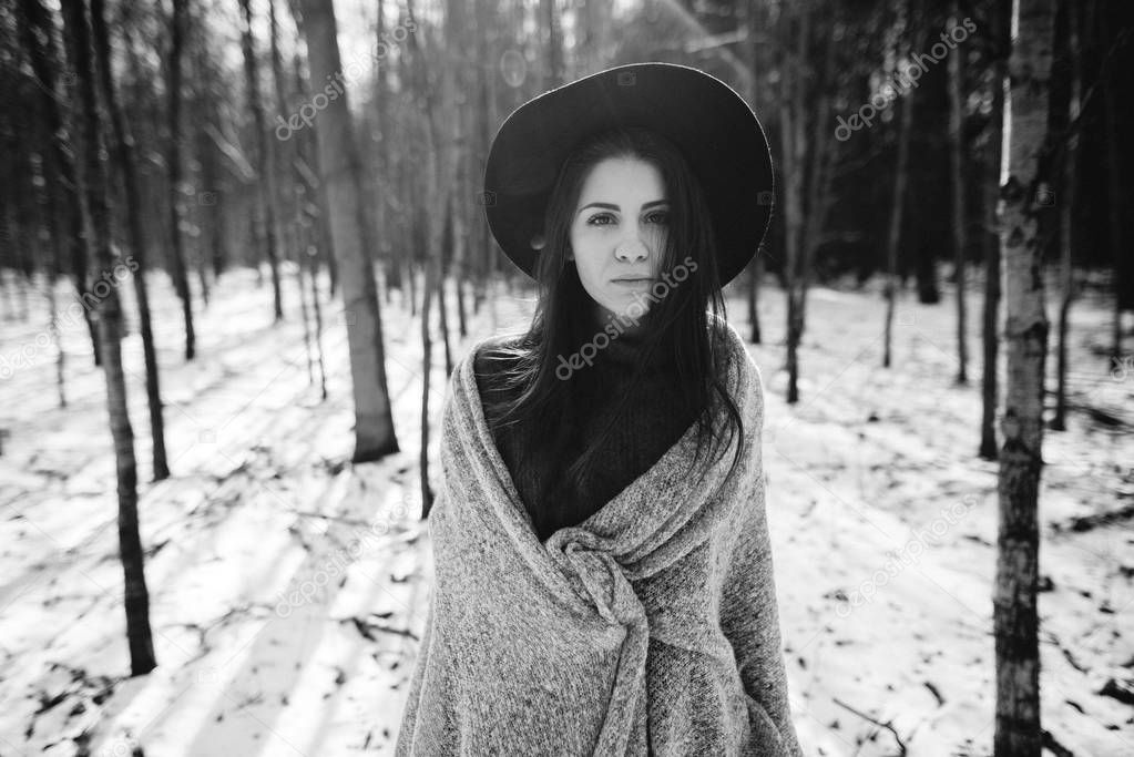 Young beautiful stylish girl in  hat walking in winter forest