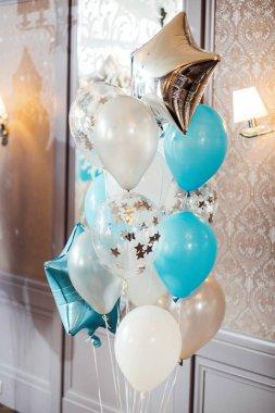birthday photo zone with white, blue and transparent balloons, free space. Colorful balloons background,