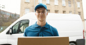 Photo Portrait of young courier in mask standing near delivery car and holding carton box