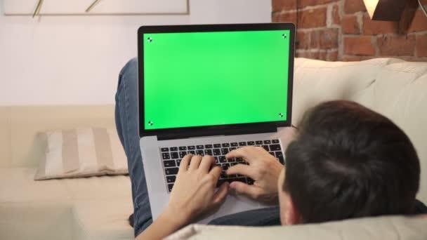 Osoba u stolu si prohlíží internet na zelené obrazovce notebooku. V dobře osvětleném, útulném bytě. Muž tam pracuje.