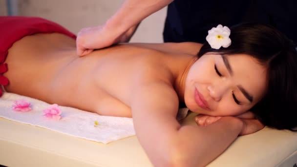 Mužský masér masíruje záda dívce asijského vzhledu. Relaxační a tonická masáž.