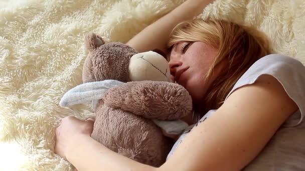 Spící dívka s plyšovým medvědem v ložnici doma