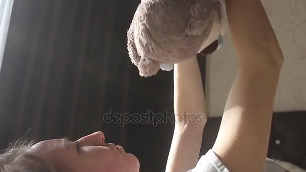Lány játszik egy macit, és mosolyogva, miközben ül ágya otthon