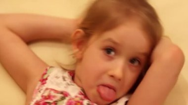 Thinking grimacing girl showing tongue with finger under face and looking  funny in camera. Vintage