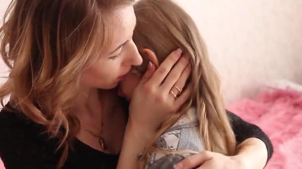hübsche Mutter beruhigend und umarmend weinendes kleines Mädchen. schöne junge Mutter beruhigt weinende Tochter zu Hause.