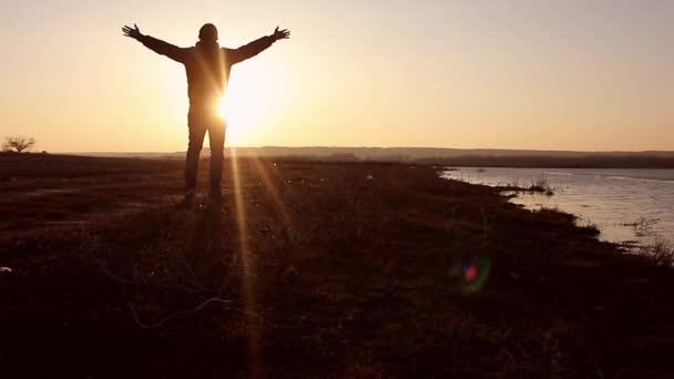 Sagoma di un uomo con le mani sollevate nel tramonto. Uomo con le sue braccia spalancate